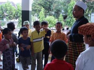 belajar memakai sarung bersama santri TPA Al-Muhtadin